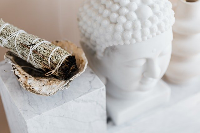 a wrap of sage and a white buddha head statue in a spiritual setting